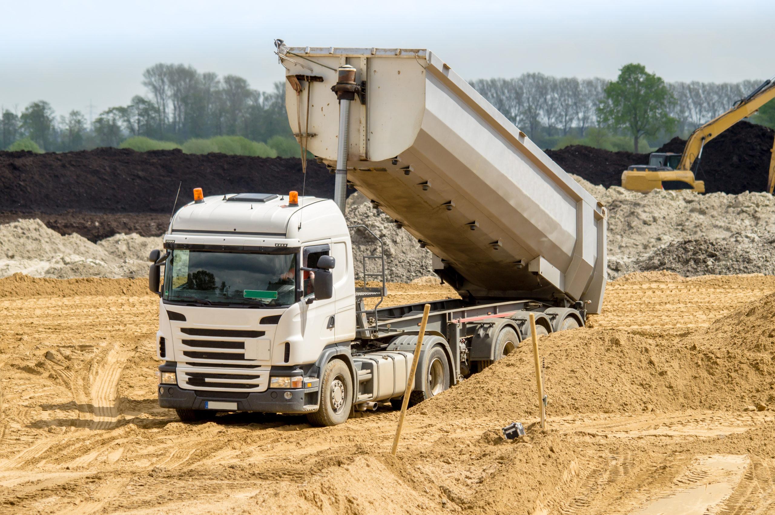 Straßenbau - Lastkraftwagen mit Auflieger kippt Sand ab