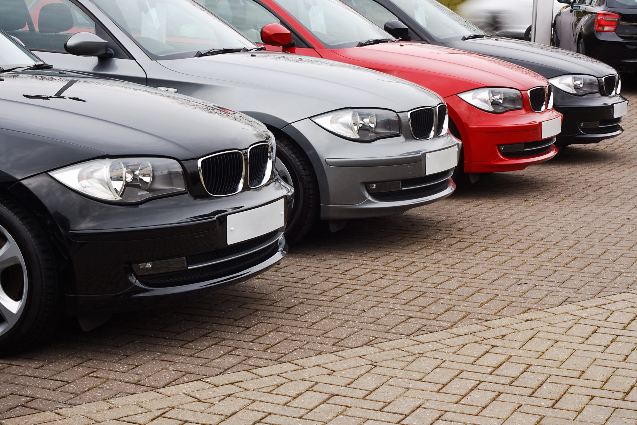 row of prestige used cars for retail sale in a motor dealers yard showing same model in different colour choices